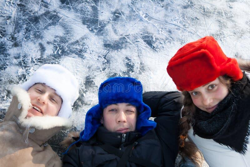 Gladlynt ungdomarsom har gyckel på snö med isbakgrund under jul, semestrar med kopieringsutrymme arkivbild