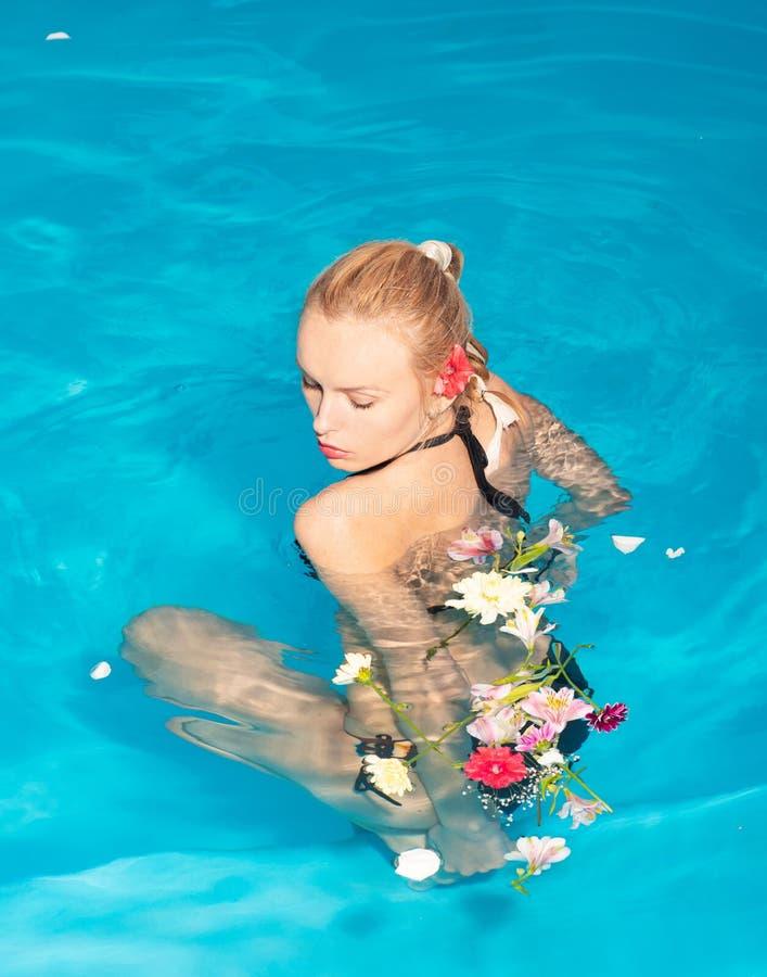 Gladlynt ungdomlig blond flicka som vilar medan utomhus- simbass?ng Lycklig ung kvinna som har gyckel p? stranden p? solig dag royaltyfria foton