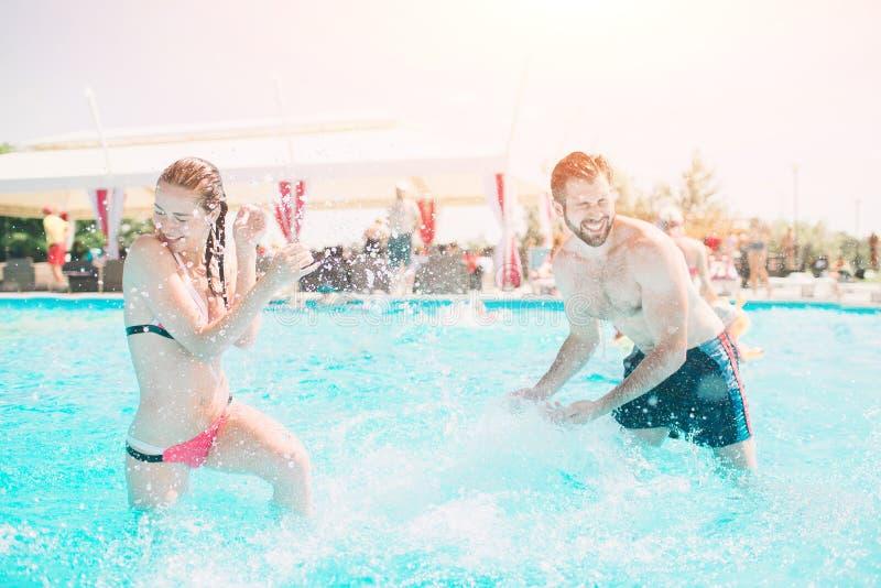 Gladlynt ungdomlig grabb och dam som vilar medan utomhus- simbassäng Koppla ihop bevattnar in Grabbar gör sommarsephi royaltyfri fotografi