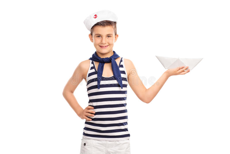 Gladlynt unge i en sjömandräkt som rymmer ett pappers- fartyg arkivfoton