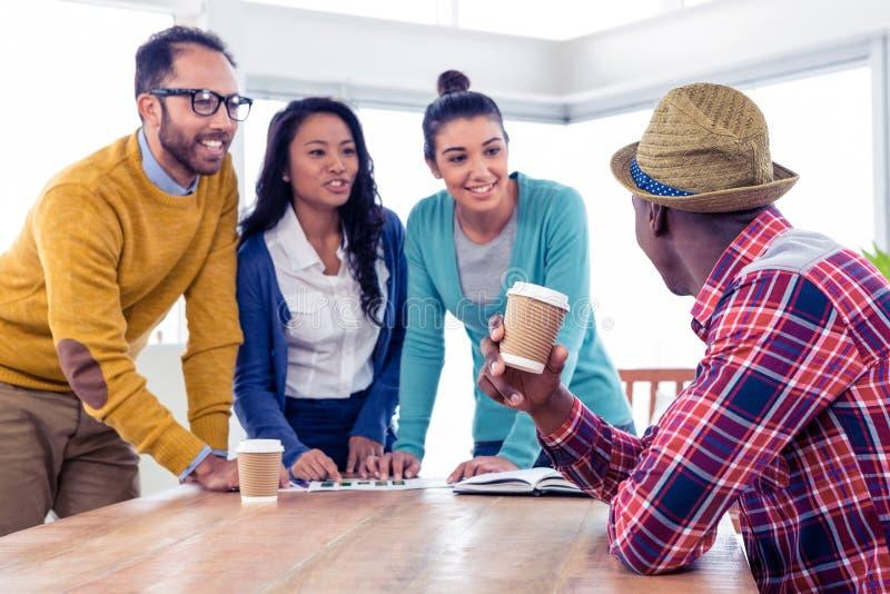 Gladlynt ungt affärsfolk som diskuterar på det idérika kontoret royaltyfri foto