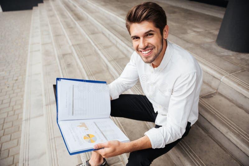 Gladlynt ungt affärsmansammanträde och läs- affärsplan i mapp royaltyfria bilder