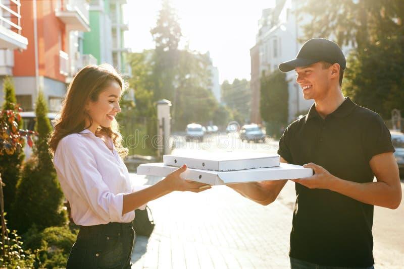 Gladlynt ungt bud som rymmer en pizzaask, medan isolerat på vit Kurir Giving Woman Boxes med mat utomhus royaltyfri bild