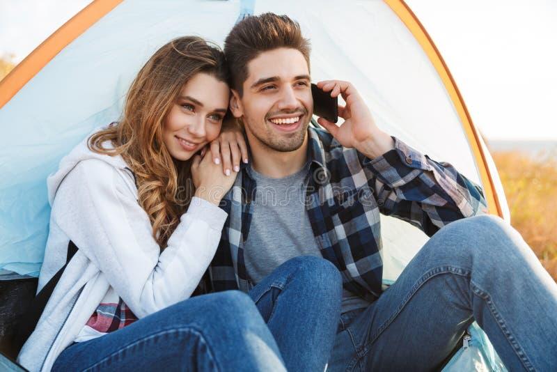 Gladlynt ungt campa för par som sitter fotografering för bildbyråer