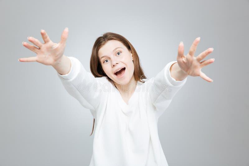 Gladlynt upphetsad tonårs- flicka som ler och når händer royaltyfria bilder