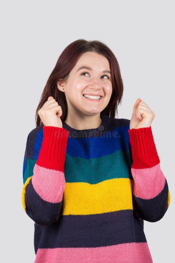 Gladlynt upphetsad ung studentkvinna som ser upp och ler arkivfoton
