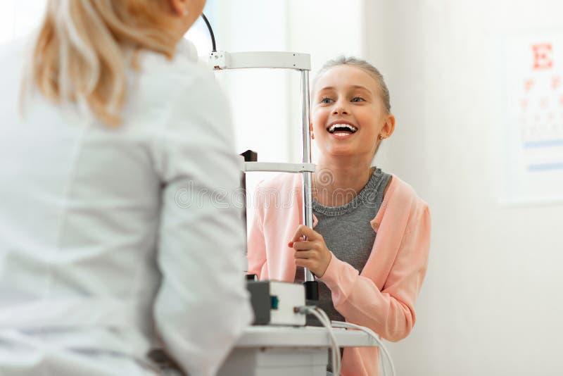 Gladlynt upphetsad unge med brett leende som talar med den angenäma doktorn arkivbilder