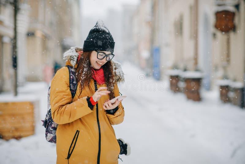 Gladlynt ursnygg brunett i smartphone för vintermodeinnehav på stads- bakgrund arkivbilder