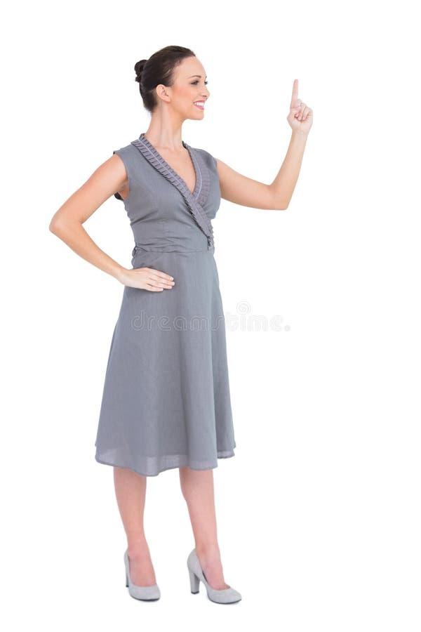 Gladlynt ursnygg kvinna i flott klänning som pekar upp hennes finger arkivbild