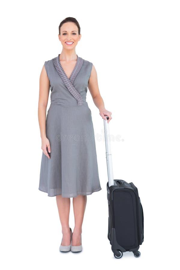 Gladlynt ursnygg kvinna med hennes posera för resväska royaltyfri foto