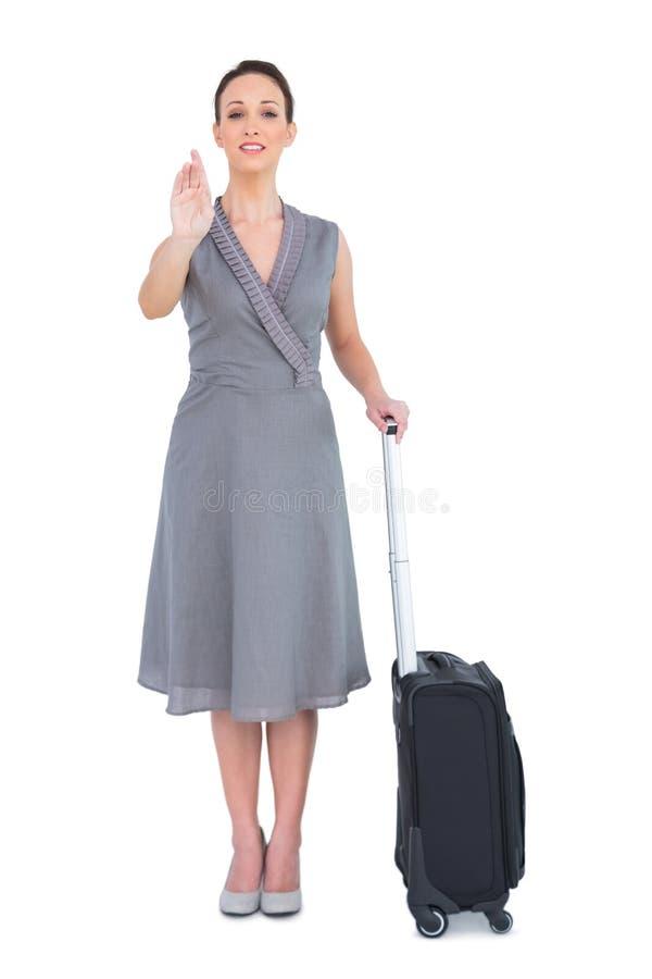 Gladlynt ursnygg kvinna med hennes resväska som ut kallar till kameran royaltyfri foto