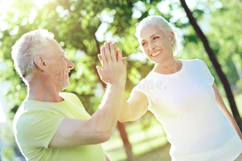 Gladlynt vänlig pensionär som ger fem till hans fru arkivfoton