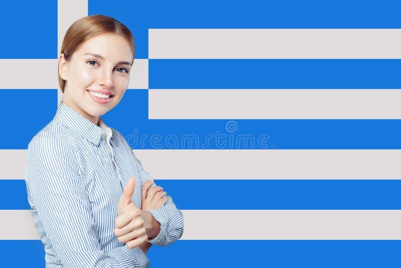Gladlynt visningtumme f?r ung kvinna upp med den Grekland flaggan royaltyfri bild