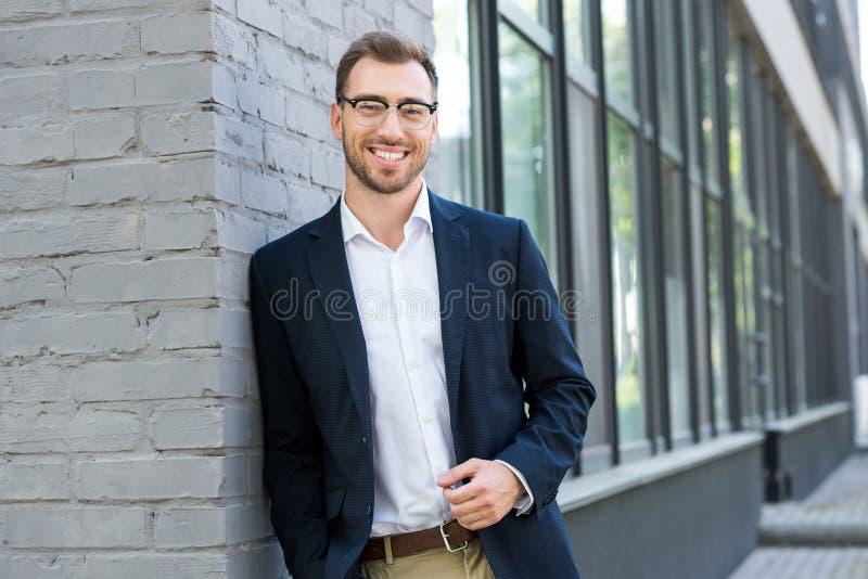 gladlynt yrkesmässig affärsman som poserar nära kontor royaltyfri foto