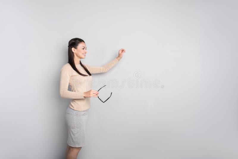 Gladlynt yrkesmässig lärarinna som står nära bräde arkivfoto