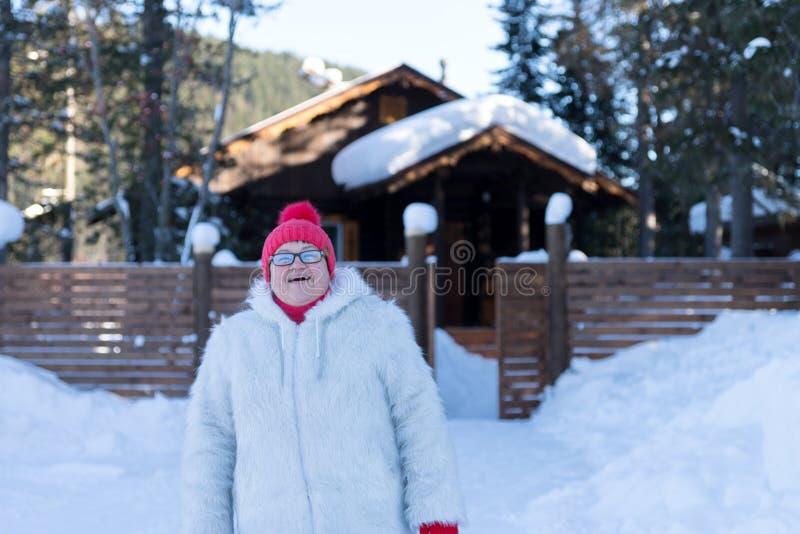 Gladlynta äldre kvinnaställningar och leenden lyckligt framme av ett lantligt trähus bland snödrivorna i skogen royaltyfria foton