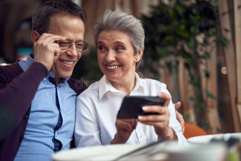 Gladlynta åldriga par som ser mobiltelefonen arkivbild