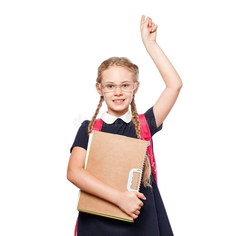 Gladlynta 8 år gammal skolflicka med ryggsäcken som bär enhetligt anseende som isoleras över vit bakgrund klar skola royaltyfri foto