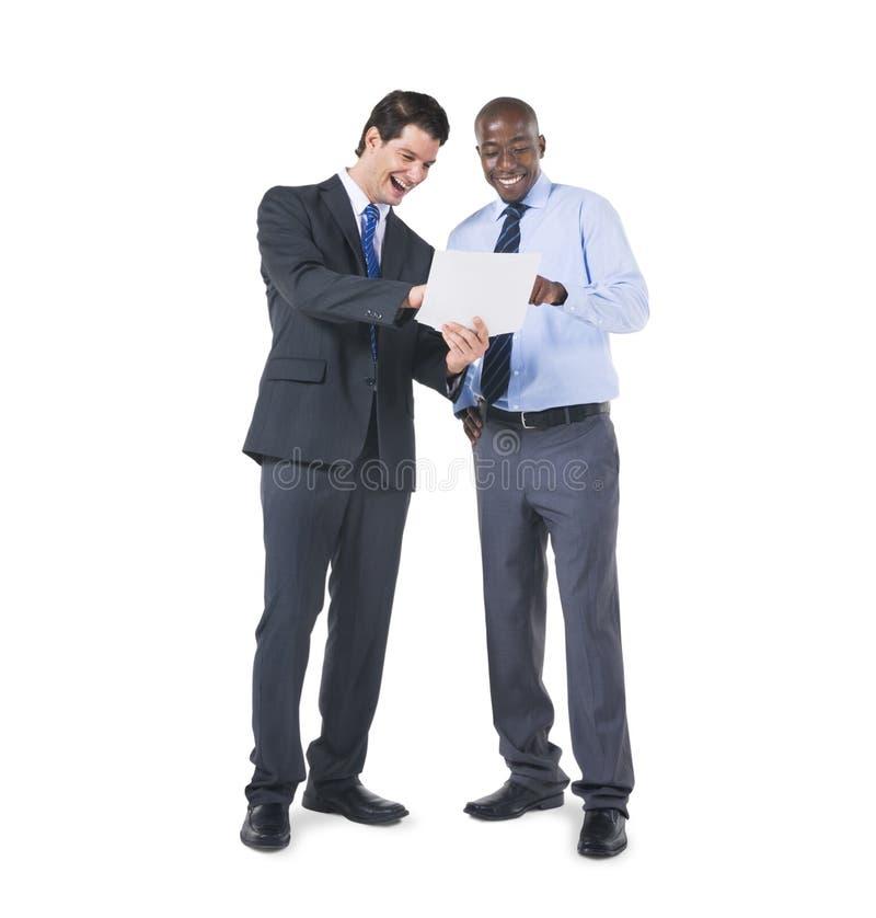 Gladlynta affärskollegor som diskuterar om dokumenten arkivfoto