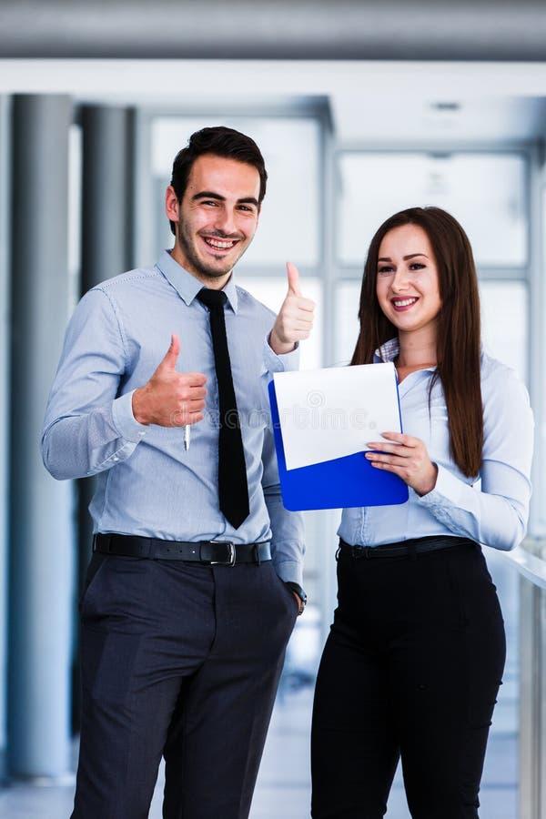 Gladlynta affärskollegor som ger upp tummar arkivfoton