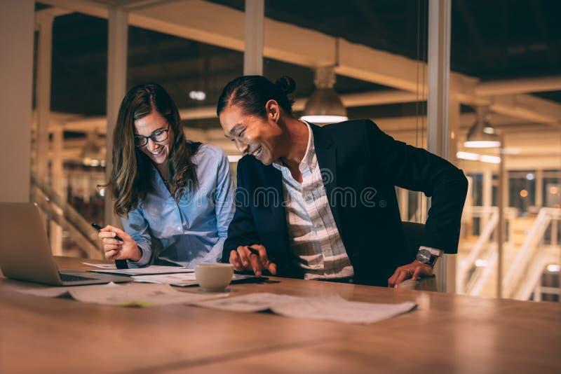 Gladlynta affärspartners som sent i regeringsställning arbetar - natt arkivbilder