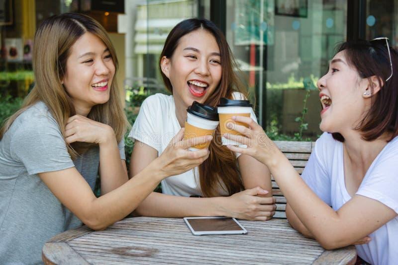 Gladlynta asiatiska unga kvinnor som sitter i kafét som dricker kaffe med vänner och tillsammans talar royaltyfria foton