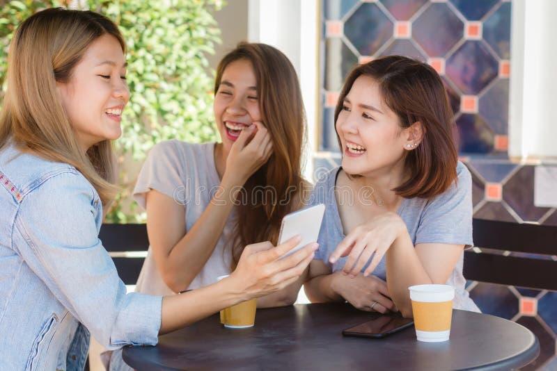 Gladlynta asiatiska unga kvinnor som sitter i kafét som dricker kaffe med vänner och tillsammans talar arkivbilder