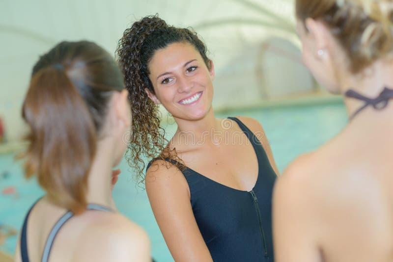3 gladlynta attraktiva flickor som pratar nära simbassäng fotografering för bildbyråer