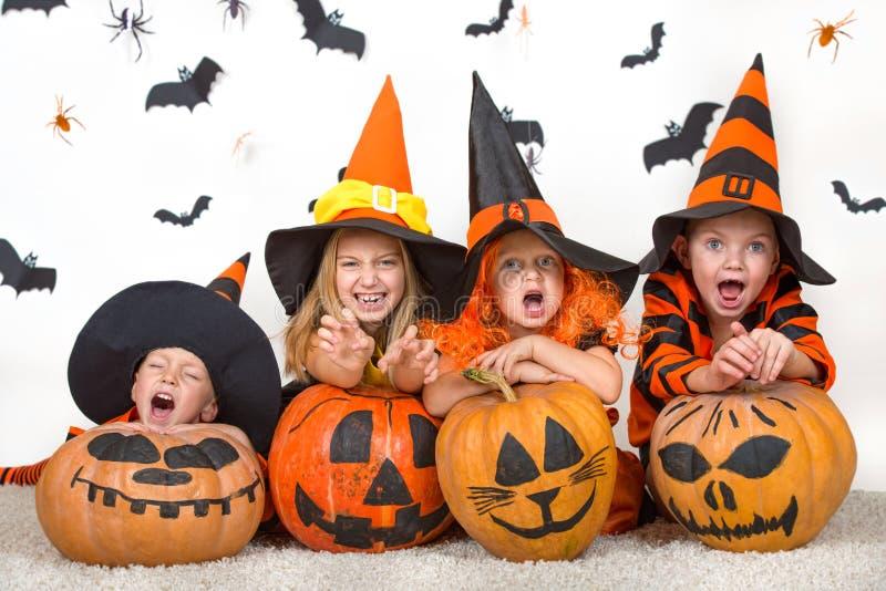 Gladlynta barn i halloween dräkter som firar halloween arkivfoto