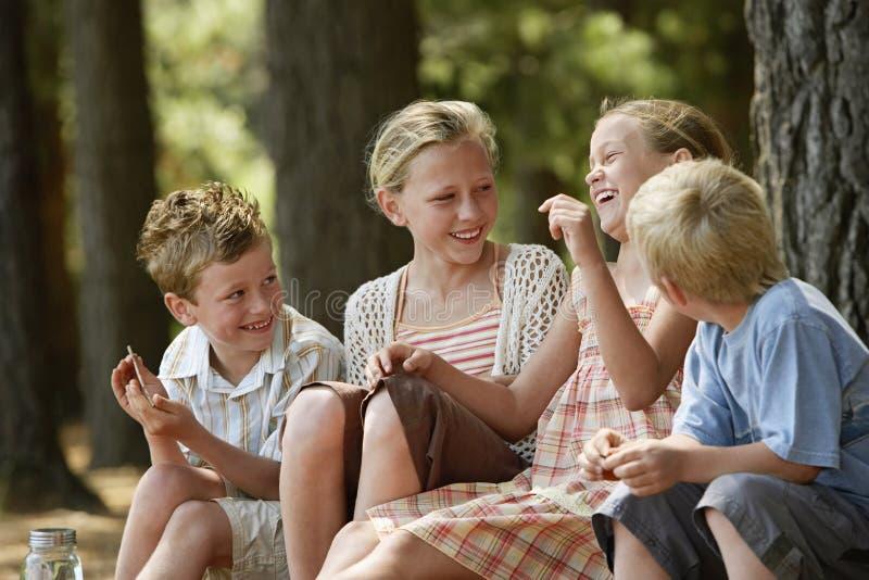 Gladlynta barn som sitter i skog royaltyfria bilder