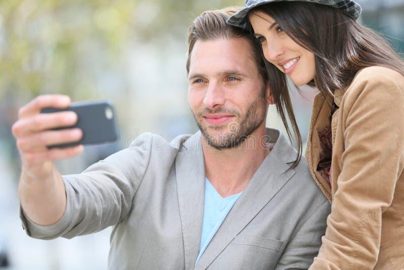 Gladlynta barnpar som tar selfie i stad royaltyfri foto