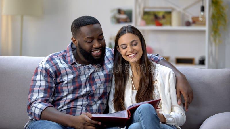 Gladlynta blandad-lopp par som hemma beskådar familjfotoalbumet, nöjeminnen arkivfoto