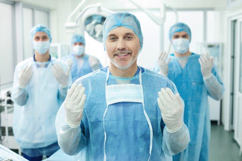 Gladlynta doktorer förbereder sig för kirurgisk behandling royaltyfri fotografi