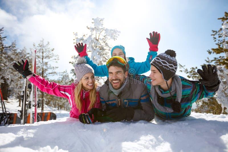 Gladlynta föräldrar med barn på snö arkivfoto