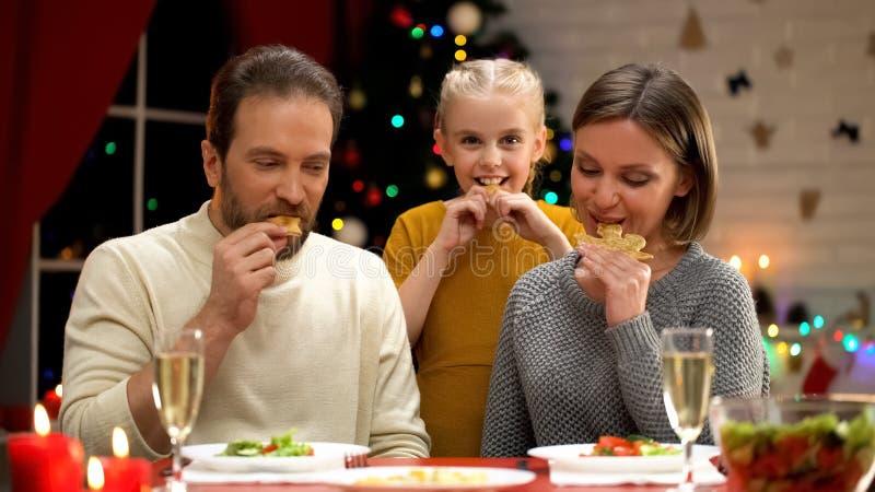 Gladlynta föräldrar och dottern som äter kakor på Xmas-helgdagsafton, semestrar tillsammans royaltyfri fotografi