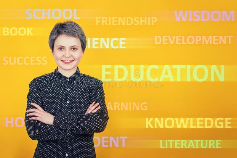 Gladlynta för ung kvinna armar för uppehällen för student eller lärarekorsade och att le planera i huvudsak framtid Olika ord sl? royaltyfri bild