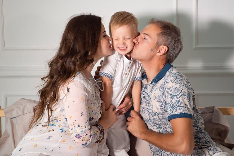 Gladlynta förväntansfulla par som hemma spelar med sonen i vardagsrum royaltyfria bilder