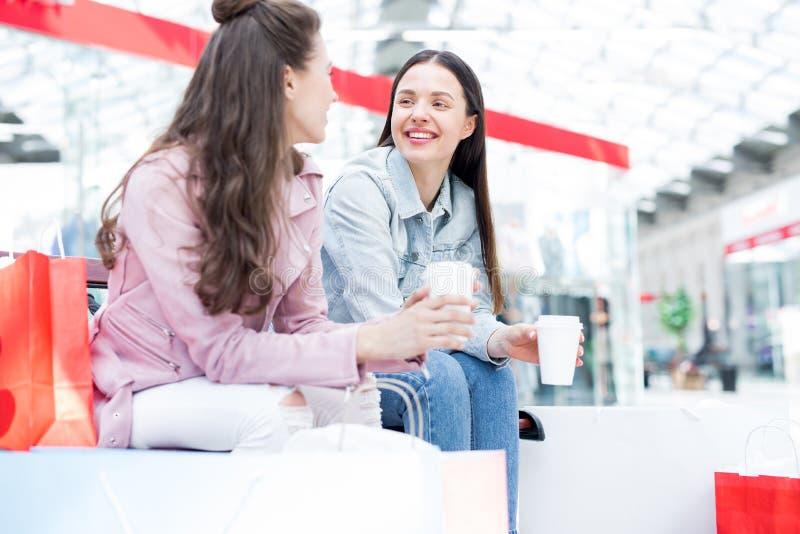 Gladlynta flickor som dricker kaffe i shoppinggalleria royaltyfria bilder