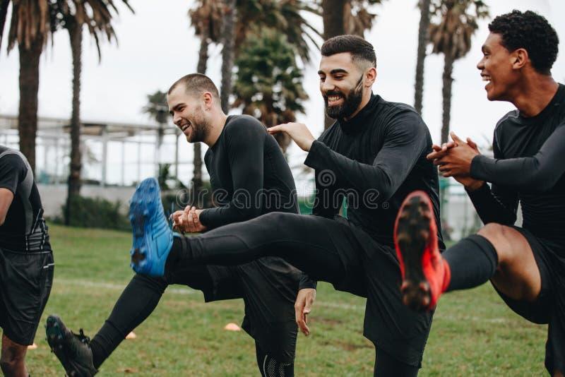 Gladlynta fotbollsspelare som gör uppvärmningsövningar på fältet för matchen Lyckliga fotbollsspelare som gör benlönelyfter som s arkivfoto