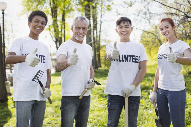 Gladlynta fyra volontärer som förbättrar, parkerar landskap royaltyfri fotografi
