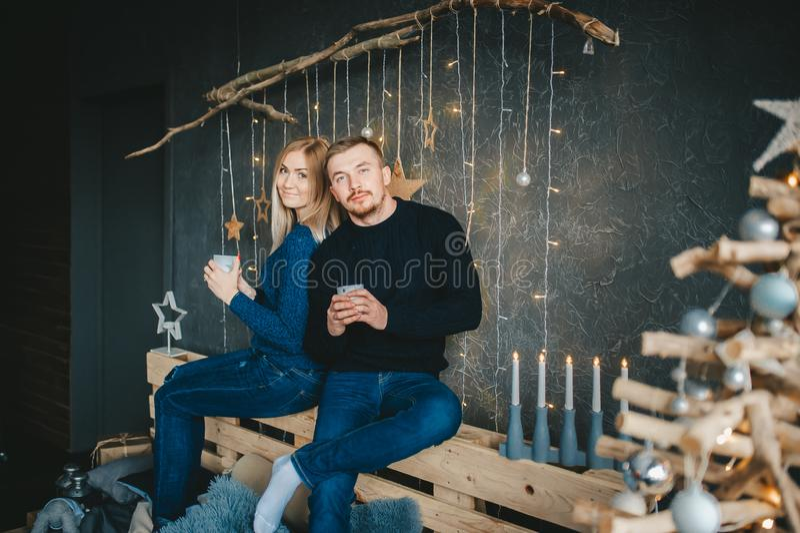 Gladlynta härliga unga par som dricker morgonkaffe nära väggen som dekoreras för jul royaltyfri bild