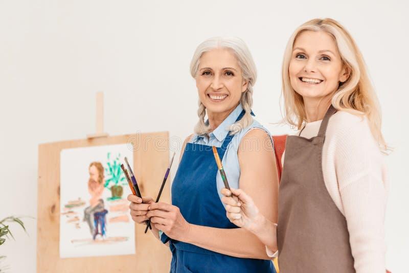 gladlynta höga kvinnor som ler på kameran och hållande målarfärgborstar arkivfoton