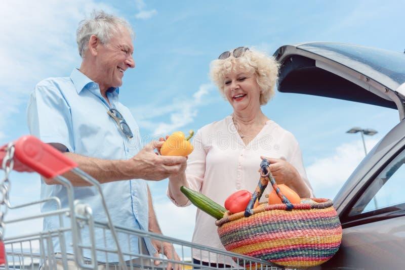 Gladlynta höga par som är lyckliga för att köpa nya grönsaker från stormarknaden arkivfoto