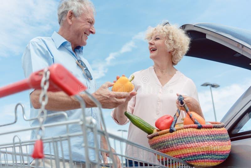 Gladlynta höga par som är lyckliga för att köpa nya grönsaker från stormarknaden arkivbild
