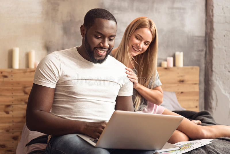 Gladlynta internationella par som hemma tycker om online-shopping royaltyfri bild