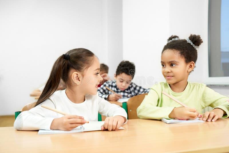 Gladlynta klasskompisar som sitter på tabellen i klassrum på skola royaltyfria bilder