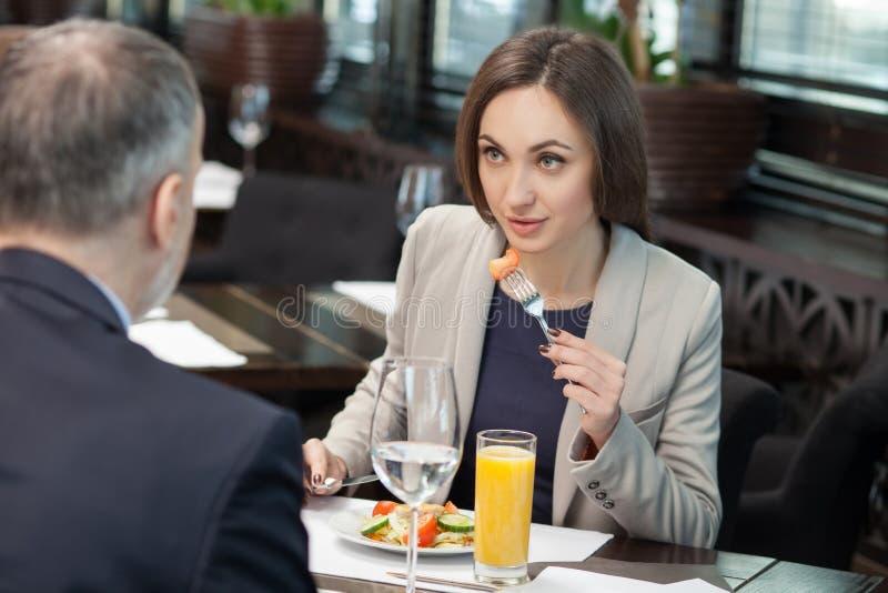 Gladlynta kollegor har ett möte i restaurang royaltyfri bild