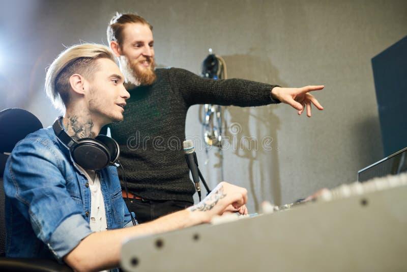 Gladlynta kollegor som gör musik i studio royaltyfria foton