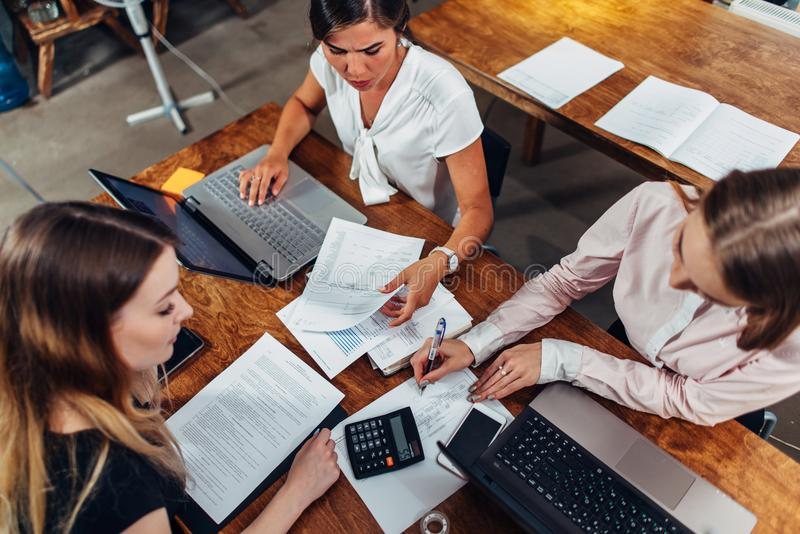Gladlynta kvinnliga affärspartners som har ett möte som diskuterar försäljningsstrategier i ett konferensrum royaltyfria foton