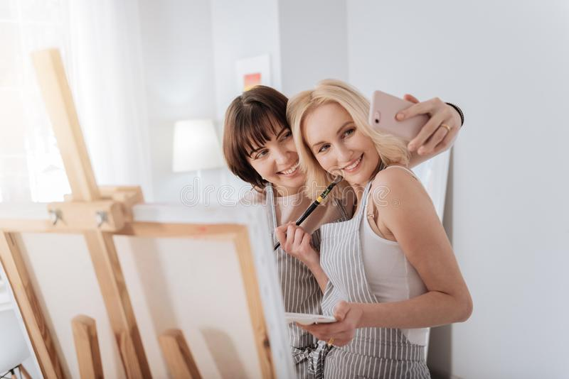 Gladlynta kvinnliga konstnärer som tar en selfie arkivbilder